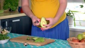 Panza y manos de la mujer embarazada que pelan apagado el aguacate en cocina en casa almacen de video