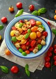 Panzanella Tomato salad with red, yellow, orange cherry tomatoes, capers, basil and ciabatta croutons. summer healthy Royalty Free Stock Images