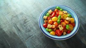 Panzanella tomatsallad med röda, gula orange körsbärsröda tomater, kapris, basilika och ciabattakrutonger Sund sommar Arkivfoton