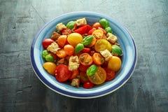 Panzanella tomatsallad med röda, gula orange körsbärsröda tomater, kapris, basilika och ciabattakrutonger Sund sommar Royaltyfria Foton