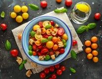 Panzanella tomatsallad med röda, gula orange körsbärsröda tomater, kapris, basilika och ciabattakrutonger Sund sommar Arkivfoto