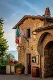 Panzano Italien - Augusti 19, 2018: Ingång till den färgrika restaurangen i Panzano med hängande flaggor arkivbild
