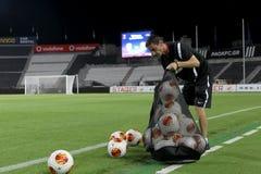 Paoks instruktör som tömmer en säck av Europaligafotboll, klumpa ihop sig Arkivbild