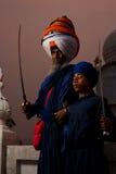 Paonta Sahib Sikh Leader & Boy. PAONTA SAHIB - MAY 22: The large turbaned gurudwara leader and a young student brandish swords at the Paonta Sahib Gurudwara stock photos
