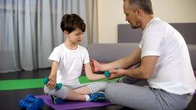 Papà allegro che insegna a suo figlio a fare le teste di legno esercitarsi a casa, potere dei muscoli immagine stock libera da diritti