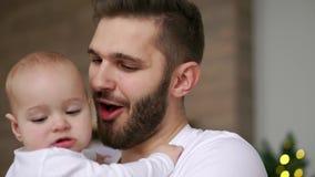 Papà barbuto che bacia bambino Chiuda su del padre felice con il bambino sulle mani Orologio commovente del bambino sulla mano de stock footage