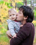 Papà che bacia il suo figlio sull'autunno esterno Fotografie Stock