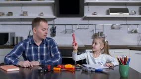 Papà che chiede alla bambina di scegliere lo strumento del cacciavite stock footage