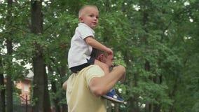 Papà che circonda un bambino sulle sue spalle stock footage