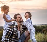 Papà che gioca con due piccole figlie sveglie immagine stock