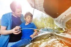 Papà che mostra il suo livello di olio del figlio in motore di automobile fotografia stock libera da diritti
