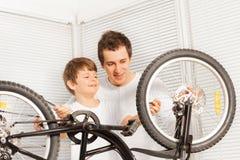 Papà che mostra a suo figlio del bambino come riparare bicicletta Fotografia Stock Libera da Diritti