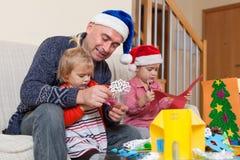 Papà con due figlie che fanno i mestieri immagini stock