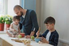 Papà con il suoi piccoli figlio e figlia che cuociono insieme immagini stock libere da diritti