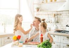 Papà con le figlie che preparano pizza Immagine Stock Libera da Diritti