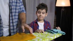 Papà d'aiuto del figlio per piegare i vestiti rivestiti di ferro a casa video d archivio
