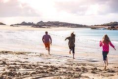 Papà e due figlie che corrono lungo la spiaggia Fotografia Stock Libera da Diritti