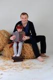 Papà e figlia nel vestito nazionale ucraino con un Abo del libro Fotografia Stock Libera da Diritti