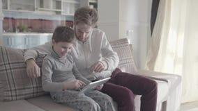 Papà e figlio che utilizza compressa digitale che si siede sullo strato nel grande salone Relazione fra il genitore ed il bambino video d archivio