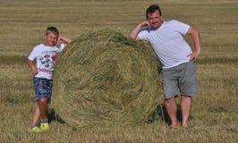 Papà e figlio vicino al mucchio di fieno Immagini Stock Libere da Diritti