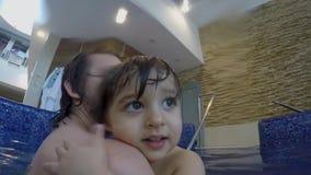 Papà e piccolo nuoto del figlio nello stagno dell'interno stock footage