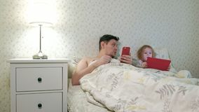 Papà e poca figlia sul letto che gioca sulla compressa stock footage