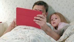 Papà e poca figlia sul letto che gioca sulla compressa archivi video