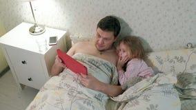 Papà e poca figlia sul letto che gioca sulla compressa video d archivio