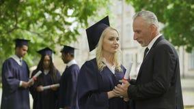 Papà emozionante che si congratula figlia laureata in parco vicino all'accademia, felicità stock footage