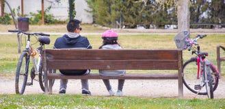 papà, ragazza e le loro biciclette al parco Il papà e la ragazza sono ciclisti che riposano ad un banco marrone che godono di un  immagini stock libere da diritti