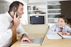 Papà sul computer portatile e sullo studio del bambino. Immagine Stock