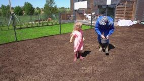 Papà sveglio del padre di aiuto della figlia della ragazza con l'erba del prato inglese che semina semina nell'iarda della casa video d archivio