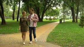Papá adulto que camina con el amor de la hija adolescente en el parque, compartiendo su experiencia de la vida metrajes