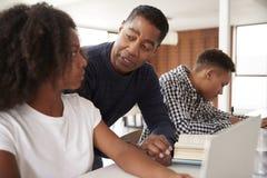 Papá afroamericano envejecido medio que ayuda a sus niños adolescentes con la preparación, ángulo bajo, cierre para arriba fotos de archivo