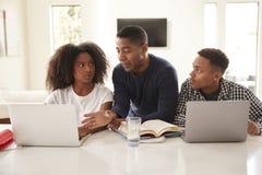 Papá afroamericano envejecido medio que ayuda a sus niños adolescentes con su preparación, vista delantera, cierre para arriba fotografía de archivo libre de regalías