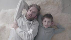 Papá barbudo y su pequeño hijo que mienten en la alfombra blanca de la piel y tener conversación interesante Charla del padre con almacen de metraje de vídeo