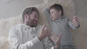 Papá barbudo y su pequeño hijo que mienten en la alfombra blanca de la piel y tener conversación interesante Padre-niño almacen de metraje de vídeo