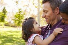 Papá blanco con sus dos niños jovenes de la raza mixta en un parque imagen de archivo