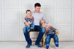 Papá con dos niños en sus rodillas que se sientan en la silla delante de la pared blanca lifestyle Niños en suéteres idénticos Imagenes de archivo