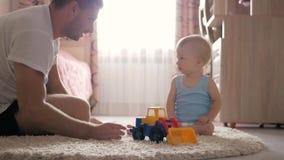 Papá con el bebé que juega con los coches del juguete en casa almacen de metraje de vídeo