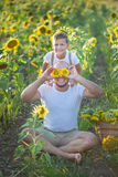 Papá con el hijo que abraza en un campo de girasoles Abrazo del hijo su padre en un campo de girasoles Imagenes de archivo