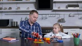 Papá con la hija del preadolescente durante la clase casera de la tienda almacen de video