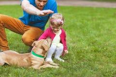 Papá con la hija que juega en el parque con su perro fotografía de archivo libre de regalías