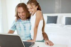 Papá con su hija que usa el ordenador portátil Imagenes de archivo