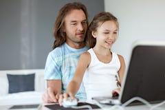Papá con su hija que usa el ordenador portátil Foto de archivo libre de regalías