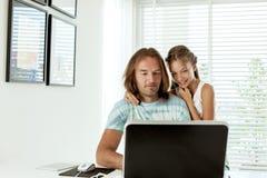 Papá con su hija que usa el ordenador portátil Imagen de archivo libre de regalías