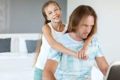 Papá con su hija que usa el ordenador portátil Foto de archivo