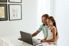 Papá con su hija que usa el ordenador portátil Fotografía de archivo libre de regalías