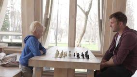 Papá con su hijo que juega a ajedrez metrajes
