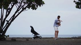 Papá con un bebé en la playa con un cochecito almacen de metraje de vídeo
